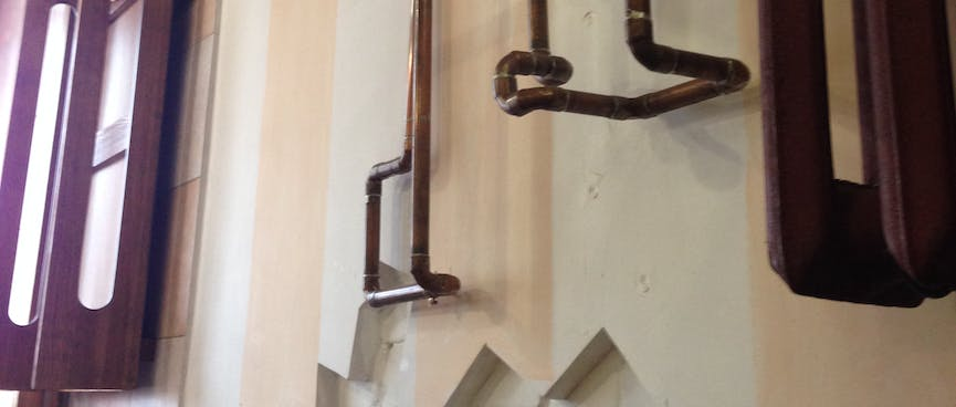 Curved bronze piping adorns the restaurant wall.