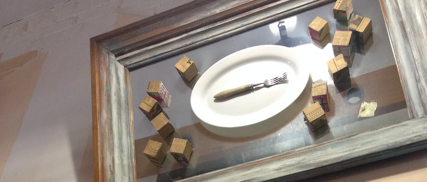 An artwork contains a dinner plate, a fork, and many small cubes.