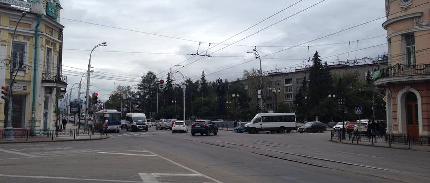 A large intersection is crossed by buses, vans, cars, tram lines and trolley bus wires.