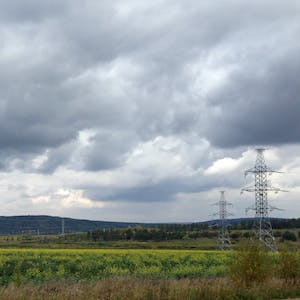 View enlargement of Power pylons in green fields.
