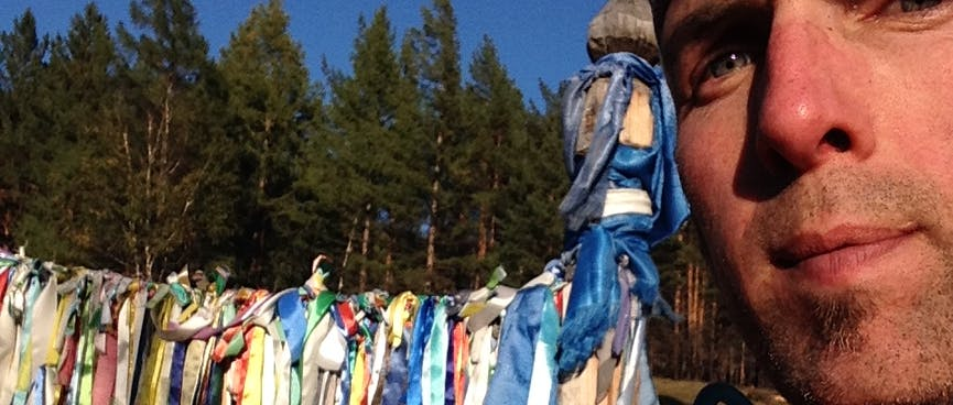 I pose in front of a line of prayer flags.