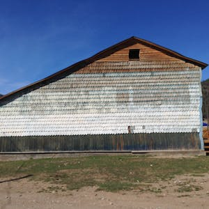 View enlargement of A large wooden barn is covered in wooden tiles.