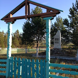 View enlargement of A small stone memorial sits behind an elaborate teal wooden gate.