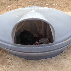 View enlargement of A large, covered saucer-shaped rubbish bin.