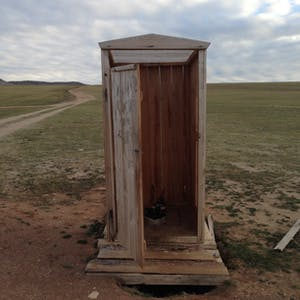 View enlargement of A wooden outhouse.