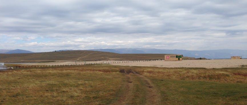 A grassy track passes a sandbar.
