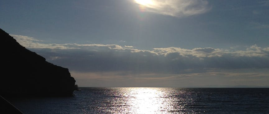 A bright sun reflects in the ocean.
