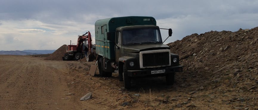 A truck and a digger on the side of the road.