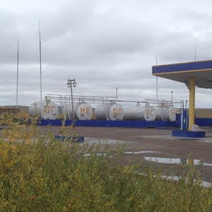 View enlargement of A row of storage tanks containing different types of gasoline.