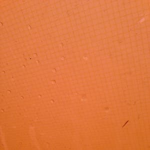 View enlargement of Rain drops sit on the bright orange fly of my tent.