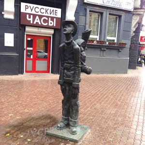 View enlargement of A metal statue of a boy wearing a hat and a backpack.