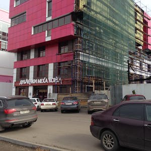 View enlargement of Square windows and pink tiles on a new building.