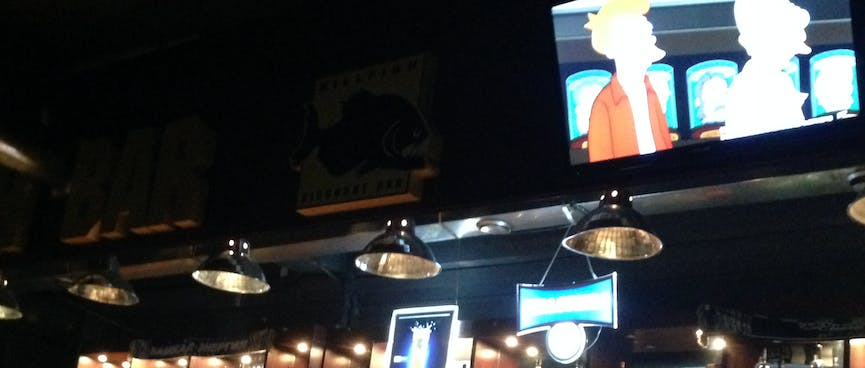 Above the bar, Futurama plays on a flatscreen TV.