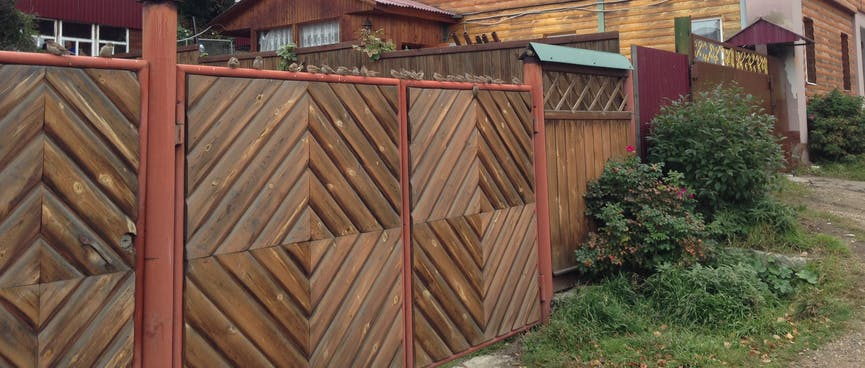 A fence is decorated with diagonal wooden slats.