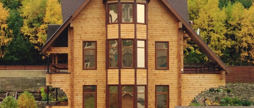 Thirteen windows on the frontage of a three story wooden house.