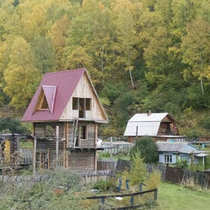 View enlargement of A three story wooden house reminiscent of a children's tree house.