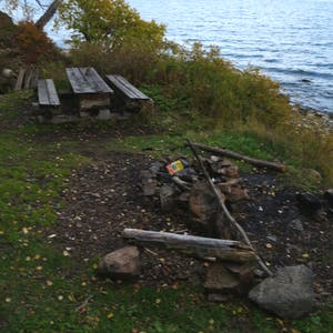 View enlargement of A used fire pit on the lake edge.