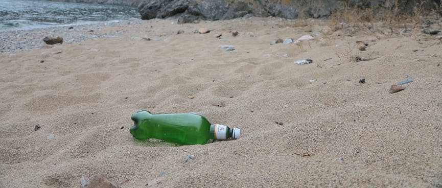 A clear green beer bottle on a sandy beach.