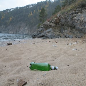 View enlargement of A clear green beer bottle on a sandy beach.