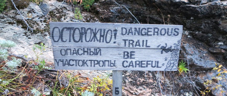 A bilingual wooden sign shows a hiker falling down a rocky bank.