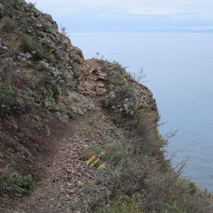 View enlargement of A narrow path hugs the side of a steep bank.