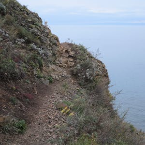A narrow path hugs the side of a steep bank.