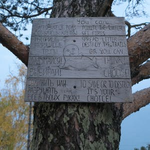 View enlargement of A wooden sign implores campers to take care of their surroundings.
