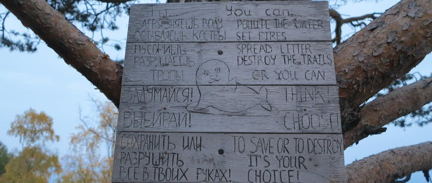A wooden sign implores campers to take care of their surroundings.
