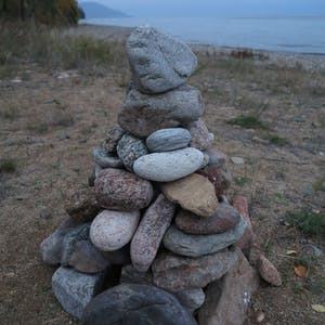 Large rocks are stacked up on the beach.