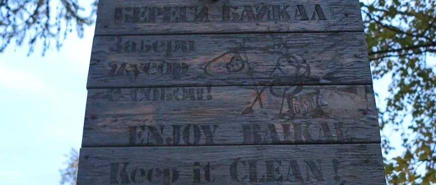 A wooden sign reads: ENJOY BAIKAL. Keep it CLEAN!