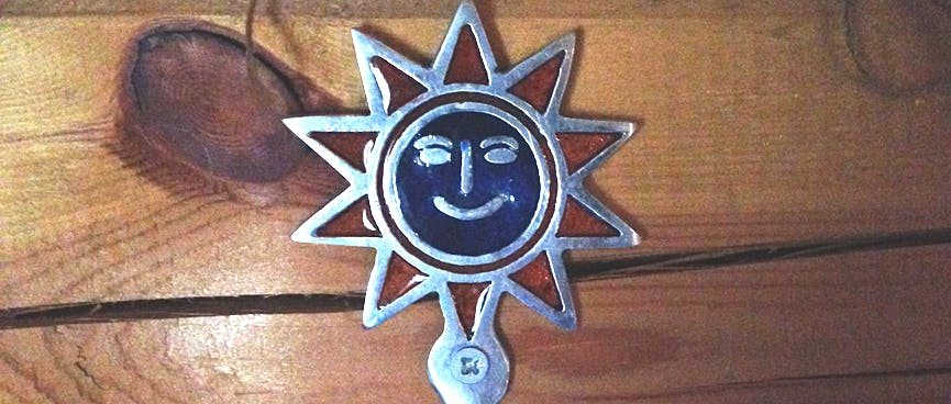A metal coat hook adorned with a smiling sun.