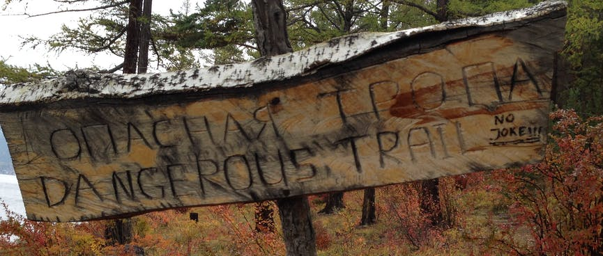 """A bilingual homemade sign reads """"DANGEROUS TRAIL""""."""