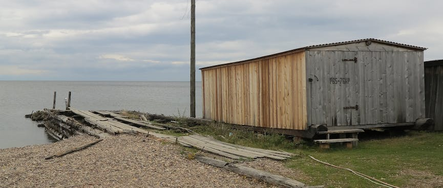 A small wooden jetty next to a boat house.