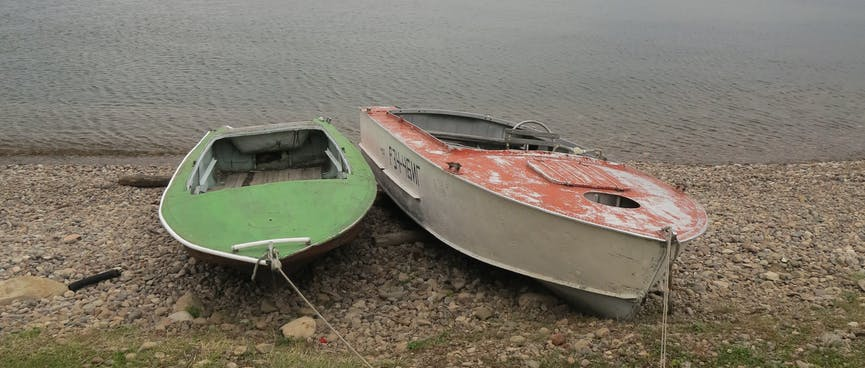 Red and green boats on the beach, tied up side by side.