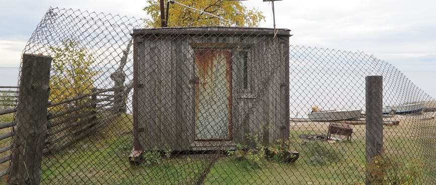 A rusty hut behind a wire mesh fence.
