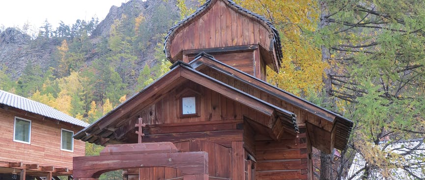 A very small wooden church sits behind a tall wooden gate.