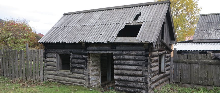 An abandoned house with a large hole in the roof.