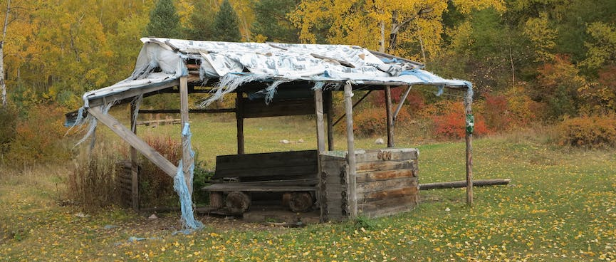 A wooden bench under a frayed plastic roof.