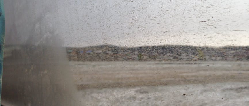 Hills and snow covered ground seen through a dirt spattered window.