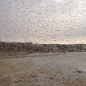 View enlargement of Hills and snow covered ground seen through a dirt spattered window.