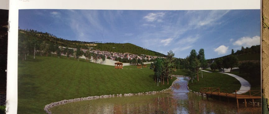 Brochure page showing modern low rise apartments on the grassy bank above a round lake.