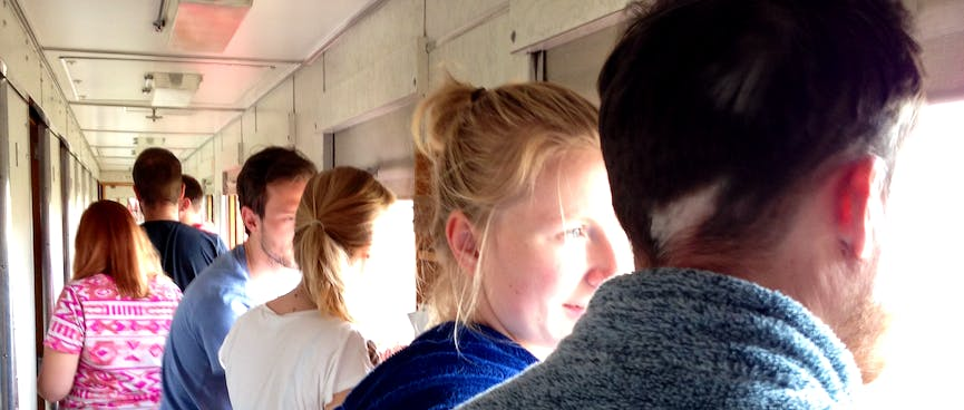 Train passengers discuss the view while standing in the aisle of a carriage.