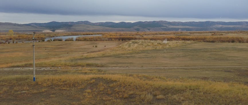 Panoramic landscape, with a grassy foreground, a tree lined river and low mountains in the distance.