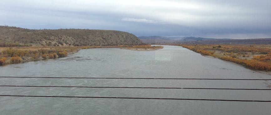 A wide river cuts through the brown countryside.