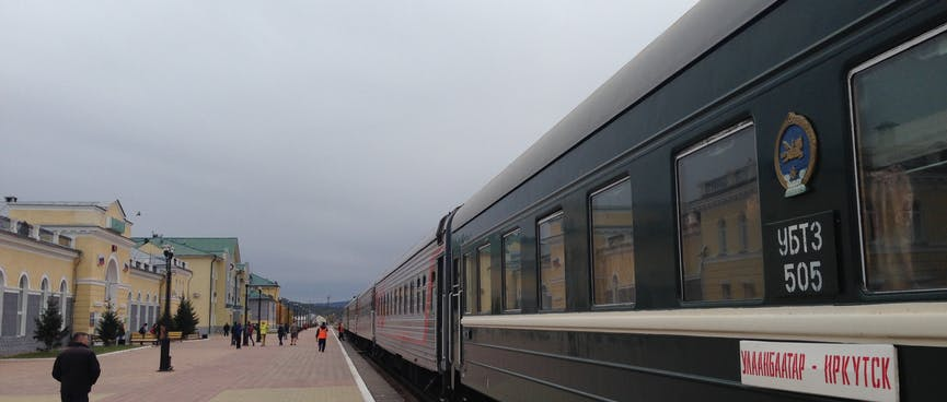 A long train parked outside the railway station.