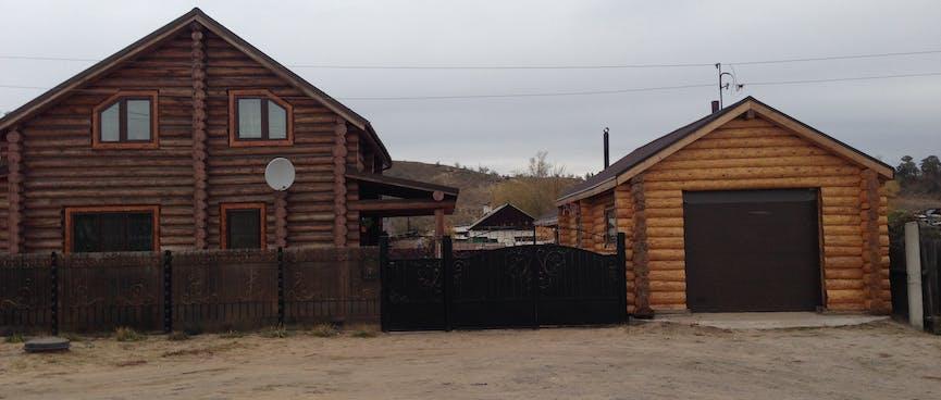 Dark log house with a lighter log garage.