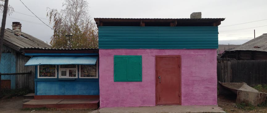 A small building is painted pink, with a red door and green shutters over the window.