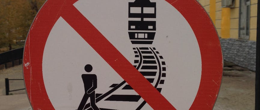 Round no entry sign depicting a man walking on the tracks while a train approaches from behind.