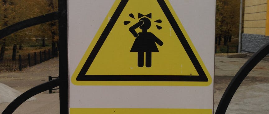 Triangle warning sign depicting a small girl crying.