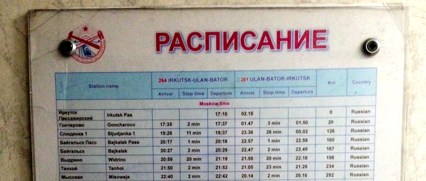 """An rectangular sign titled """"РАСЛИСАНИЕ"""" (schedule) containing columns of places and times."""